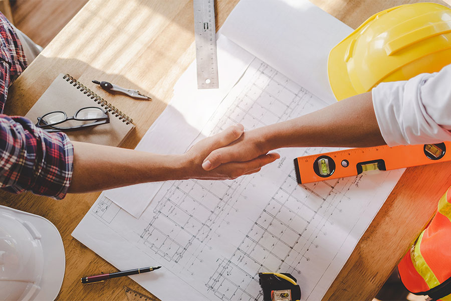 Specialized Business Insurance - Contractor And Client Shaking Hands Over Desk With Building Plans