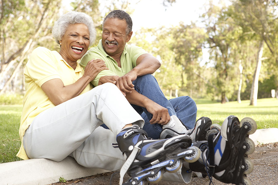 Other Insurance - Laughing Elderly Couple At The Park Putting On Rollerblades